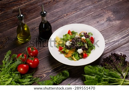 Delicious salad with salmon fillet, aromatic herbs, spices and vegetables. Healthy food, diet or cooking concept. - stock photo