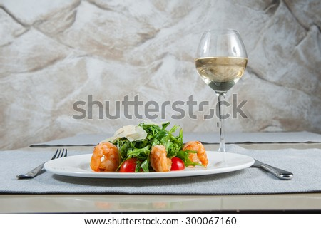 Delicious salad with shrimps, arugula, cherry tomatoes and Parmesan cheese, seasoned with balsamic sauce on served for dinner restaurant table