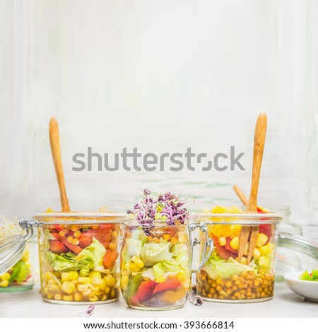 Delicious salads in glass jars with vegetables, lenses, corn and sprouts on light wooden background, side view, place for text. Healthy lifestyle or diet food concept - stock photo
