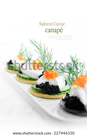 Delicious salmon caviar and cream cheese canapes against white. Copy space. - stock photo