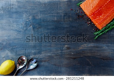Delicious salmon fillet, aromatic spices and lemon on dark wooden background with space for text. Vegetarian food, health or cooking concept. Top view. - stock photo