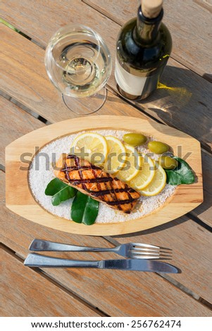 delicious salmon fillet grilled served on a wooden plate with lemon, olives and sea salt on wooden table in restaurant with white wine - stock photo