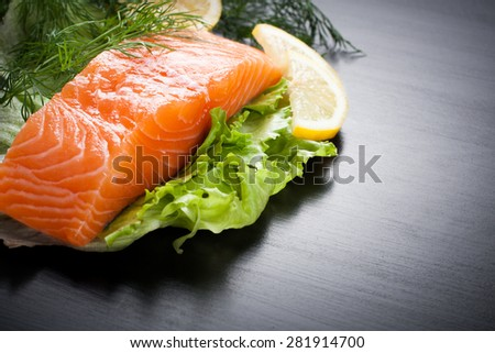 Delicious salmon fillet, rich in omega 3 oil, aromatic spices and lemon on fresh lettuce leaves on black wooden background. Healthy food, diet and cooking background with copy space. - stock photo