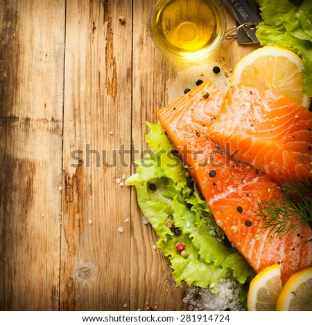 Delicious salmon fillet, rich in omega 3 oil, aromatic spices and lemon on fresh lettuce leaves on rustic wooden background. Healthy food concept. With copy space. Retro style toned. Top view. - stock photo