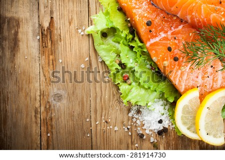 Delicious salmon fillet, rich in omega 3 oil, aromatic spices and lemon on fresh lettuce leaves on rustic wooden background. Healthy food, diet and cooking concept. With copy space. Top view. - stock photo