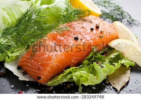 Delicious salmon fillet, rich in omega 3 oil, aromatic spices and lemon on fresh lettuce leaves on black wooden background. Healthy food, diet and cooking concept. - stock photo