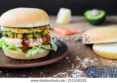 Delicious salmon sandwich with salad, avocado and pineapple. - stock photo