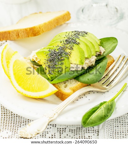 delicious sandwich of toasted bread, avocado and spinach, with chicken, sprinkle with poppy seeds on a white plate and white vintage tablecloth. Served with lemon slices. selective Focus - stock photo