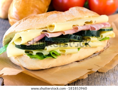 Delicious sandwich stuffed with ham,cheese and salad  - stock photo