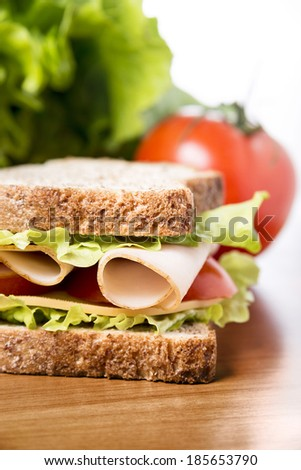 delicious sandwich with chicken breast, salad, cheese and tomatoes - stock photo