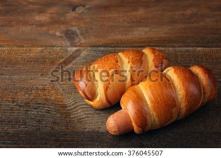 delicious sausage in the dough isolated on brown wood table