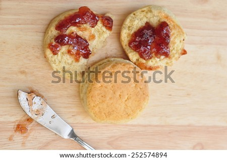 Delicious scone on wooden plate with strawberry jam - stock photo