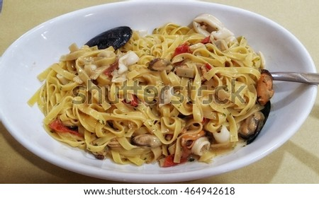 Delicious seafood pasta in white bowl.