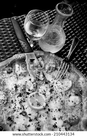 Delicious seafood pizza with scallops on wicker table in rustic pizzeria restaurant served with cold white wine in ornate pitcher. Retro aged photo. Black and white. - stock photo