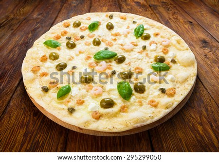 Delicious seafood pizza with shrimps, calamari rings, capers and olives - thin pastry crust at wooden table background - stock photo