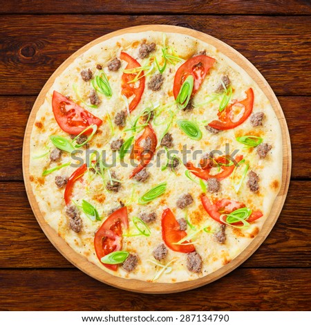 Delicious seafood pizza with tuna fish, tomatoes and leek - thin pastry crust, above view isolated at wooden background - stock photo