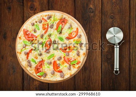 Delicious seafood pizza with tuna fish, tomatoes and leek - thin pastry crust, above view isolated at wooden background with stainless steel cutter - stock photo