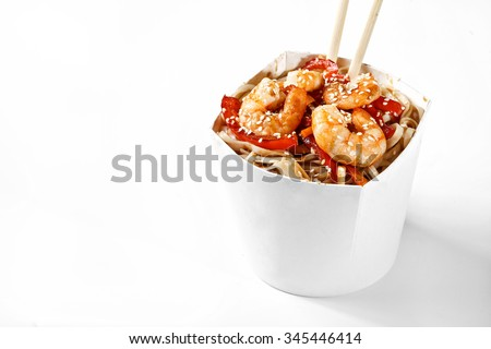 Delicious seafood wok noodles box with shrimps and udon with chopsticks. Chinese and asian takeaway fast food. Studio isolated with real shadow - stock photo