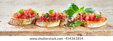Delicious seasoned savory Italian tomato bruschetta slices on a rustic wooden board garnished with fresh basil leaves, horizontal banner - stock photo