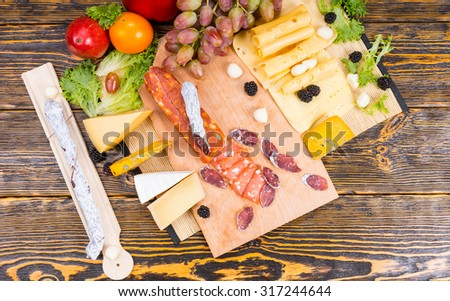 Delicious selection of different cheeses and spicy sausage displayed on a cheeseboard with grapes garnished with fresh blackberries, olives and bell peppers, overhead view - stock photo