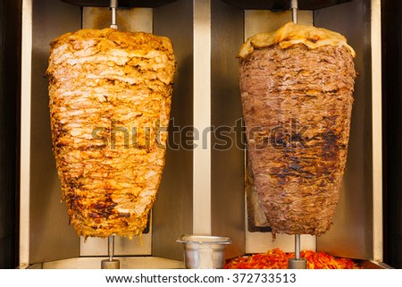 Delicious slabs of skewered fast food shawerma chicken and lamb meat turn side by side on a spit. This is part of a common sandwich found in the Middle East.