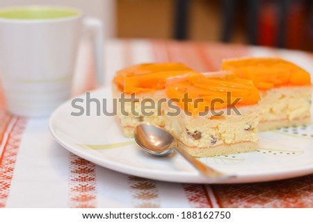 delicious slice of apricot cake lays on a white plate with a cup of cocoa on the table closeup