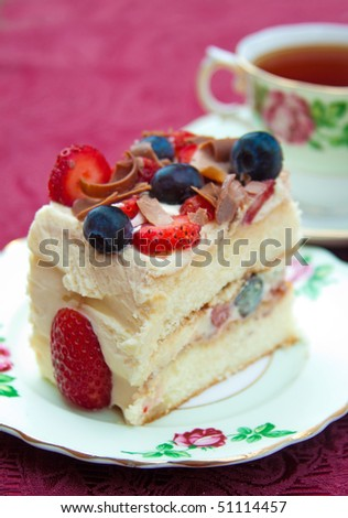 Delicious slice of berry sponge cake with strawberries, blueberries and milk chocolate shavings with selective focus on the cake.
