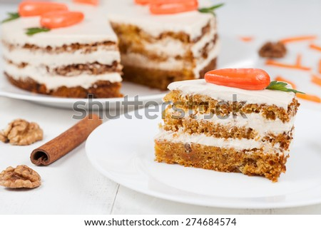 Delicious slice of carrot sponge cake with icing cream and little orange carrots on white background