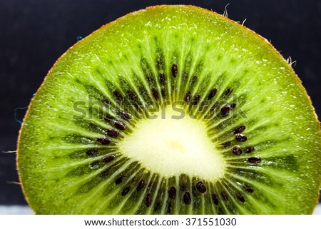 Delicious slice of juicy ripe green kiwi close up on a black background - stock photo