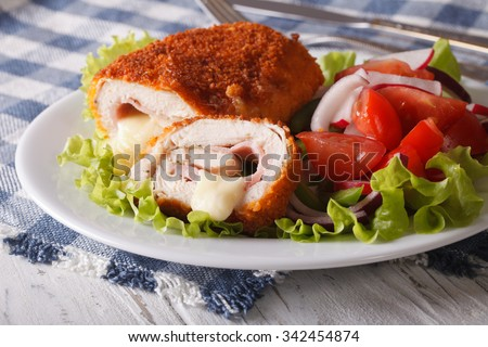 Delicious sliced Chicken cordon bleu and a salad on a plate close-up. horizontal