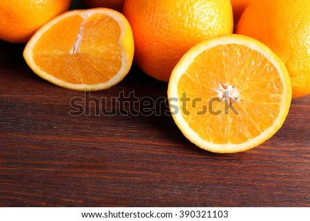 delicious sliced oranges lay in a heap on brown wooden table
