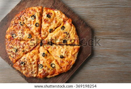 Delicious sliced pizza on wooden board, close up - stock photo