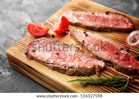 Delicious sliced steak with vegetables on board, closeup