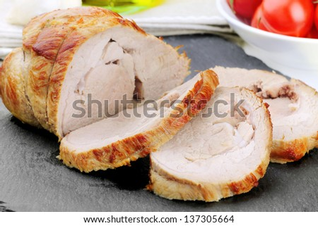 Delicious sliced veal roast on a black slate board - stock photo