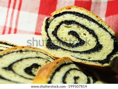Delicious slices of swiss poppy roll on picnic background - stock photo