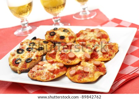 Delicious small pizza slices for snack with beer - stock photo
