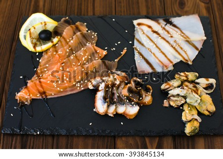 Delicious smoked salmon fish platter garnished with lemon and red caviar. Isolated on a white background. - stock photo