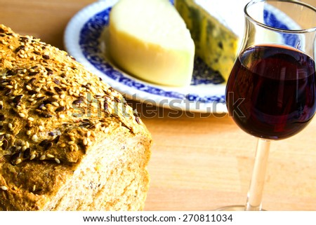 Delicious snack, bread, glass of red wine and cheese  - stock photo