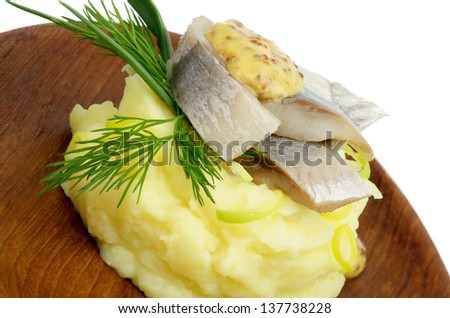 Delicious Snack of Piquant Herring on Mashed Potato with Dill, Spring Onion and Mustard on Wooden Plate - stock photo