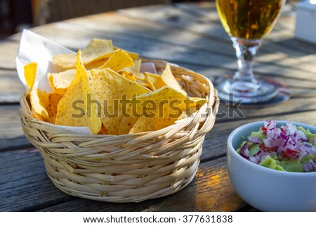 Delicious snack with nachos served in basket and accompanied by guacamole and a glass of bier, on wooden table - stock photo