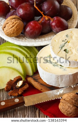 Delicious soft cheese with apple, grape and nuts for snack.
