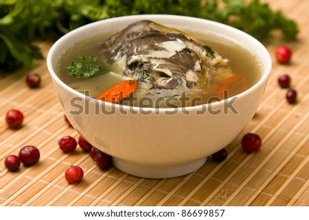 Delicious soup of the carp with potatoes, carrots and parsley - stock photo