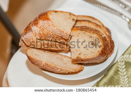 Delicious sourdough bread on white plate on party table. - stock photo