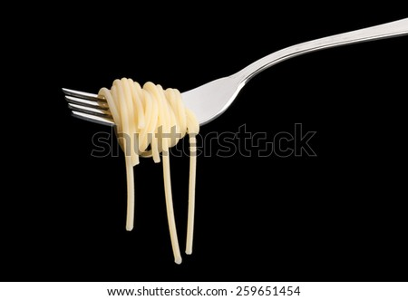 Delicious spaghetti on a fork close-up on black background