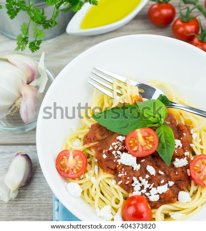 Delicious spaghetti pasta dinner in bowl garnished with three basil leaves, cheese and sliced cherry tomatoes on wooden table - stock photo