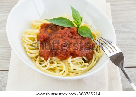 Delicious spaghetti pasta dinner in bowl garnished with three basil leaves, napkin and fork on top over wooden table - stock photo