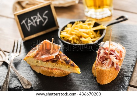 Delicious spanish tapas and beer served on a wooden table. - stock photo