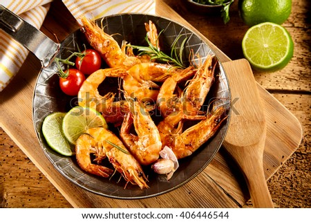 Delicious spicy grilled prawns with trimmings including fresh lime, garlic, cherry tomatoes and rosemary served in an old frying pan in a rustic country kitchen or restaurant - stock photo