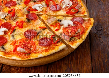 Delicious spicy pizza with mushrooms, chili peppers and pepperoni - thin pastry crust piece cut, closeup on wooden round desk at wooden background - stock photo