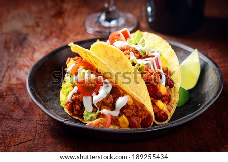 Delicious spicy tacos with meat, salsa and vegetables drizzled with sour cream and served with lemon wedges for a savory snack or lunch - stock photo